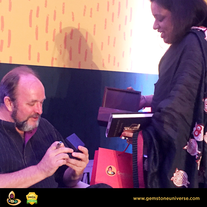 William Dalrymple admiring a bespoke Gemstone Pendant from the Gemstoneuniverse collection of Fine Jyotish Gemstones